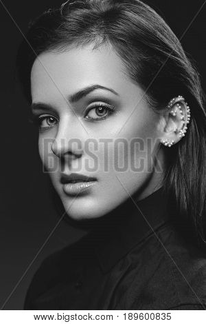 Beautiful young woman with natural make up and pearls glued on ear wearing black shirt. Beauty shot on black background. Copy space. Monochrome.