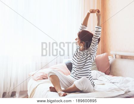 Woman doing yoga exercise on bed at home. Morning workout in bedroom. Healthy and sport lifestyle.