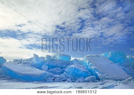 Hummocks of turquoise blue ice blocks covered with snow under white clouds