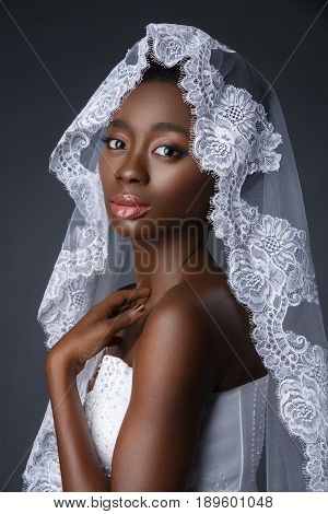 Beautiful black skin young woman in white gown and lace veil. Beauty shot on grey background. Copy space.