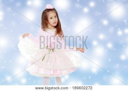 Dressy little girl long blonde hair, beautiful pink dress and a rose in her hair.She plays with her floors for her dress.Blue Christmas festive background with white snowflakes.