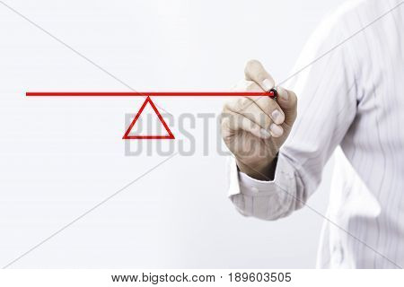 Businessman drawing a seesaw to demonstrate the concept of a lever and fulcrum of balance equilibrium and equality.