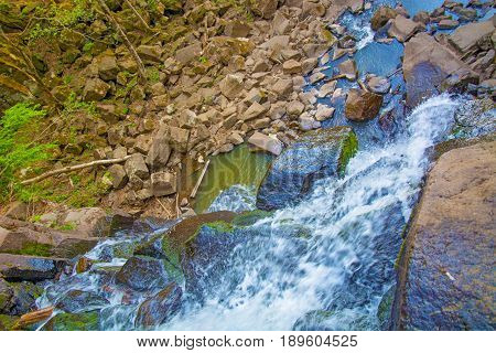 view from the top of the waterfall falling down, forest landscape with a waterfall, where begins the descent to water. Taiga
