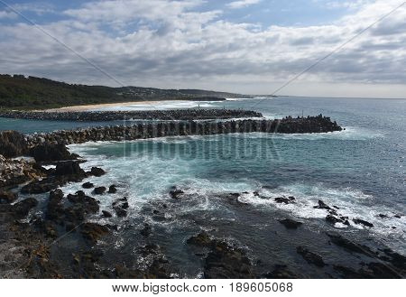 Breakwaters at Narooma (NSW Australia) on a cloudy day. Dam rock for protecting the sea erosion. The entrance of Wagonga Inlet. View from Bar Rock lookout.