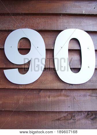 Senior man concept : House number ninety sign on wooden background