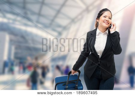 Businesswoman Talking On Mobile Phone While Carrying Luggage In Airport