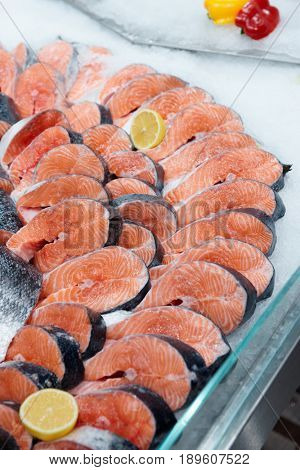 Fresh raw salmon chunks on ice in supermarket or fishmonger's shop