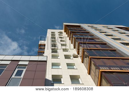 Multi-storey residential apartment buildings over blue sky, horizontal