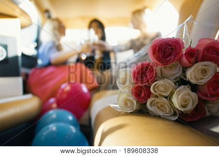 Party in limousine - happy girls celebrating, women drinks champagne - in front of bouquet of roses, close up