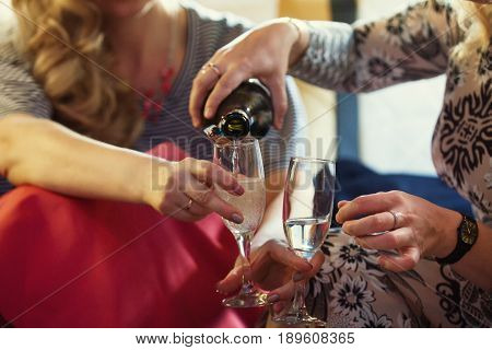 Party in limousine - happy girls celebrating, woman pour champagne, close up