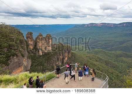 Blue Mountains Australia - May 1 2016: People at observation deck at Echo point lookout with view of famous Three Sisters mountains and Blue Mountains eucalyptus forest