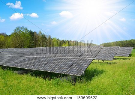 Solar power station on the spring meadow. Photovoltaic panels generate clean energy.