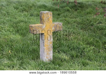 An old cross on a grave overgrown with grass in a cemetery
