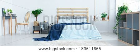 Blue design of spacious modern bedroom with wooden additions