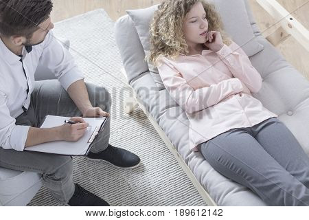 Handsome psychotherapist making notes during therapy session