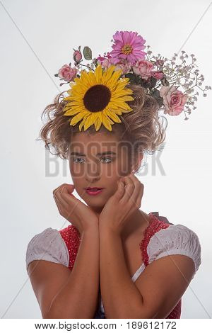 Portrait of a young woman with hairpin and summer flowers in her hair and Bavarian dirndl