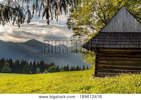 Old Wooden Mountain Chalet And Evening Mountain Ridge