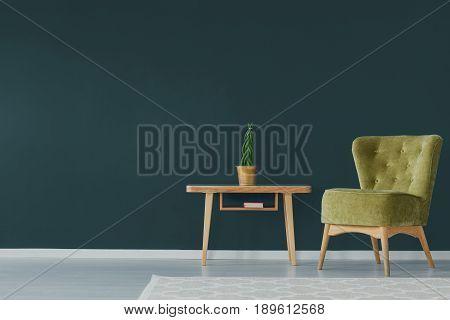 Green velvet armchair on dark turquoise wall