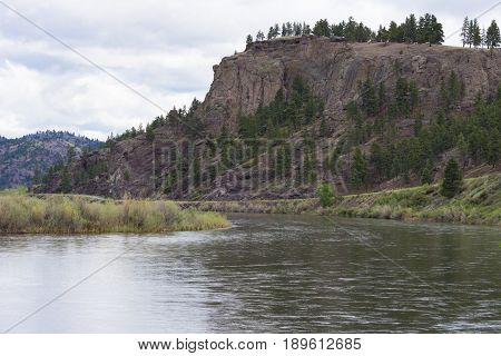 A bend in the Missouri River as it courses through rocky cliffs and willow lined banks under cloudy skies.