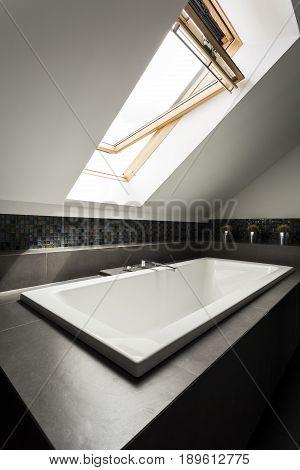 Calm and stylish bathroom at the attic with bathtub in dark tones