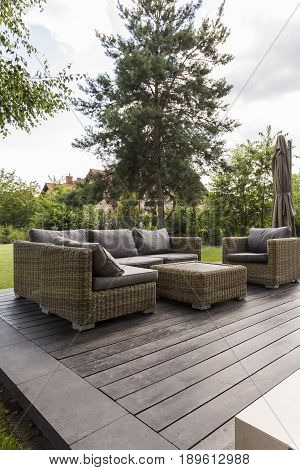 Wooden terrace at the backyard with couch armchair and coffee table