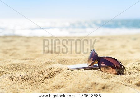Close up sunglasses and phone on the beach on warm yellow sand, with luring water sparkling on background