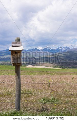 Close up of weathered bluebird house on a fence post with rugged snow capped mountains and foothills in the background.