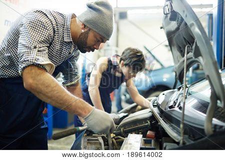Car service technician repairing engine