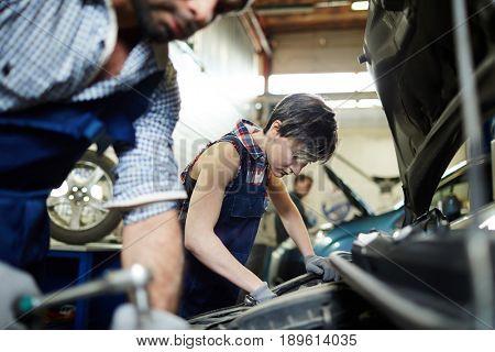 Two mechanics working in car repair service