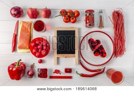 Collection of red food organized on white table, black chalkboard in center, topview