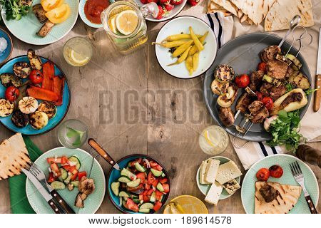 Frame made of different food cooking on the grill. Shish kebab grilled vegetables salad snacks and homemade lemonade. Dinner table concept