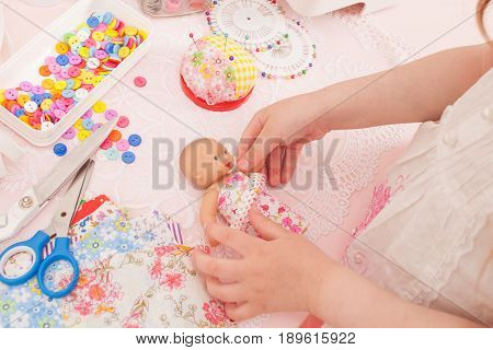 Girl playing fashion designer dressing the dolls in pieces of cloth. Next sewing machine thread buttons needles rubber and miscellaneous pieces of fabric.