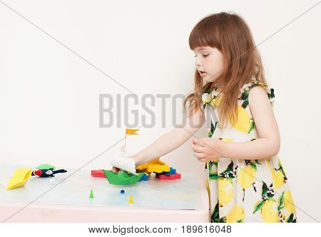 A Little Girl Playing With Paper Boats