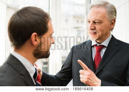 Senior businessman talking to a younger colleague