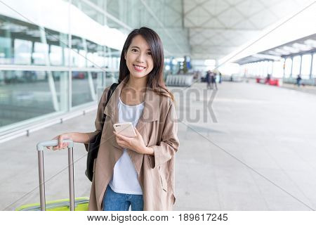 Woman travel with luggage and cellphone at airport