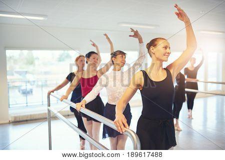 Active Adult Female Ballet Dancers Exercising In Class
