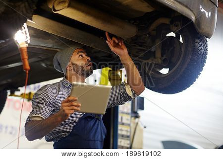 Repairman with touchpad touching detail of car while inspecting it