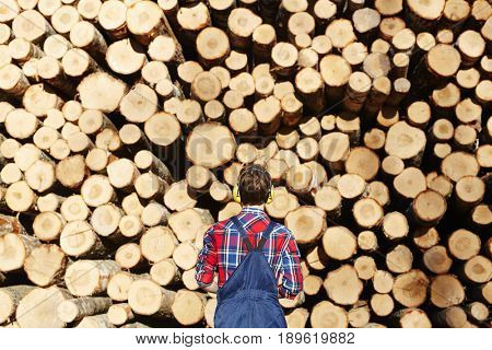 Back of man in headphones standing in front of log stack