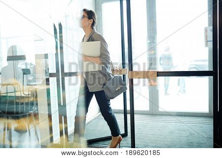 Contemporary busineswoman entering cafe to have lunch