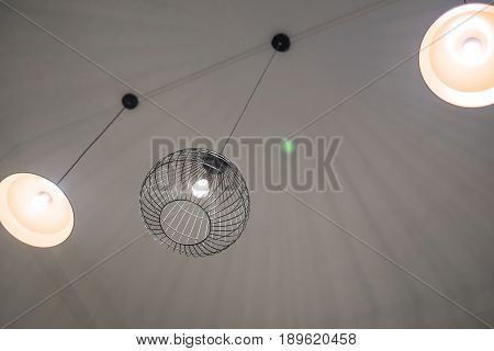 Modern ceiling lamps lighting equipment in dark room with shadow shallow focus.