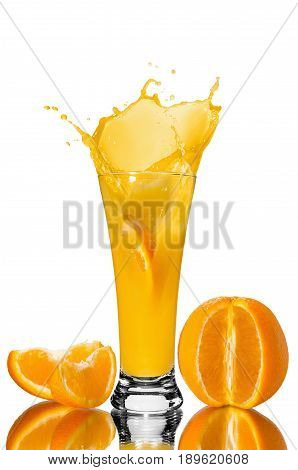 orange juice in a glass slice of orange falling into juice spray juice