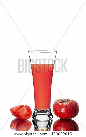 Fresh sliced tomato and a glass of tomato juice with a mirror image