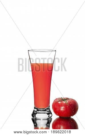 Fresh tomato and a glass of tomato juice with a mirror image
