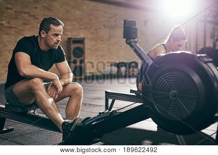 Two Young Sportive Adults Training In Gym