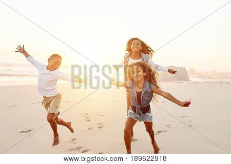 Cheerful happy black sisters and brother running and having fun together on evening beach.