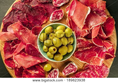 An overhead photo of a Spanish cold meats platter with jamon and payes sausage, with green olives, on a dark background