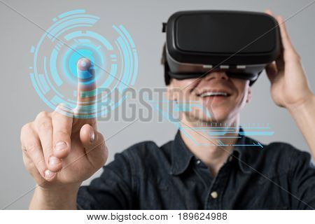 Man using virtual reality goggles on grey background