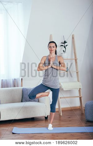Young cheerful attractive woman practicing yoga at home, working out wearing sportswear, top, pants, indoor full length