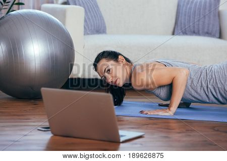 Beautiful young woman doing exercises at home looking to the laptop