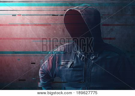 Cyber crime and network security concept unrecognizable faceless man wearing hooded jacket with digital glitch effect